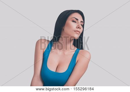 Seductive beauty. Attractive young woman with perfect cleavage keeping eyes closed while standing against grey background