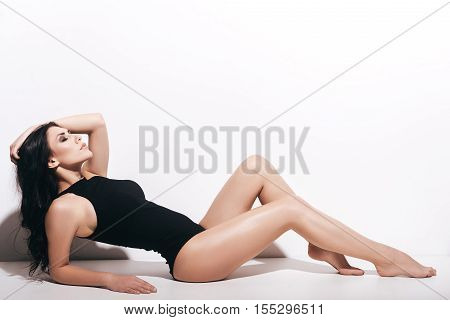 Just perfect. Side view of attractive young woman in black swimsuit holding hand in hair and keeping eyes closed while lying in front of white background