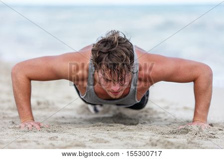 Fit fitness man exercising arms muscles doing exercise push ups exercises. Caucasian male fitness athlete model cross-training push-up on beach outdoor. Pushups trainer working out in summer on beach.