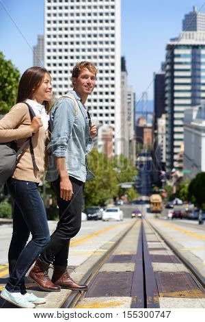 San Francisco city people lifestyle. Young interracial couple students walking on city street crossing road across railway cable car system. Famous destination tourists visiting urban city center.