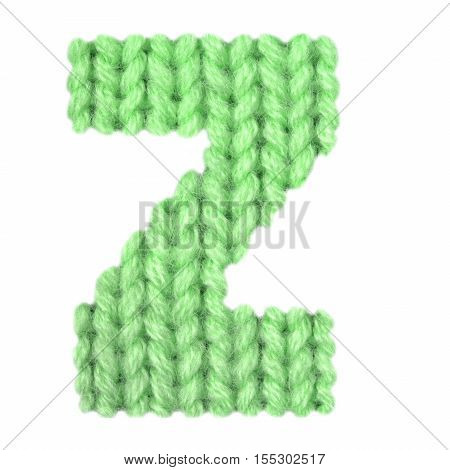 Letter Z alphabet on a blurry texture knitted pattern of woolen thread closeup. One letter of the English alphabet. Education and holidays. Typography design. Color green