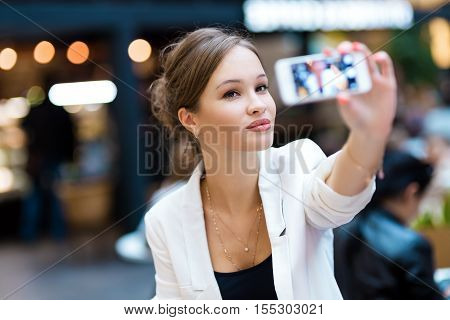 Young, beautiful girl in a white suit, shoots self