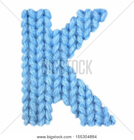 Letter K alphabet on a blurry texture knitted pattern of woolen thread closeup. One letter of the English alphabet. Education and holidays. Typography design. Color blue