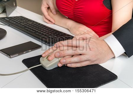 Harassment at workplace. Boss or manager is touching hand of his secretary.