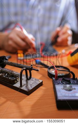 Closeup of male hands checking circuit with multimeter. Electrician repairing electronic equipment. Soldering iron on table. Selective focus