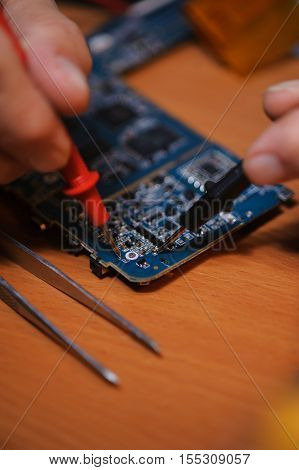 Male engineer cheching computer board with multimeter closeup. Electrician repairing electronical components.