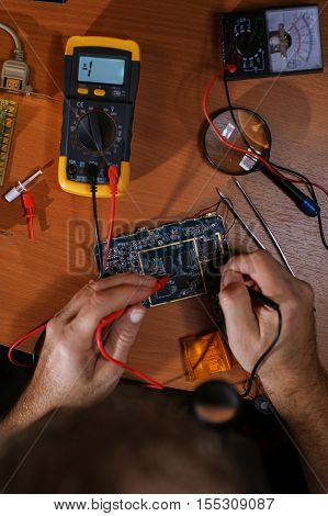Electrician checking circuit computer board with multimeter. Magnifier tester tweezers on table. Top view