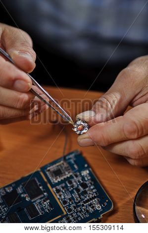 Male electronic engineer holding chip with tweezers. Electrician repairing computer board.