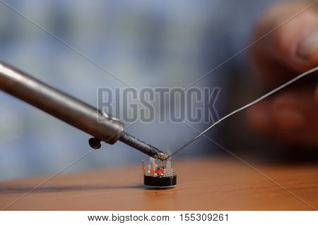 Closeup of soldering iron and wire with chip. Electronical component.