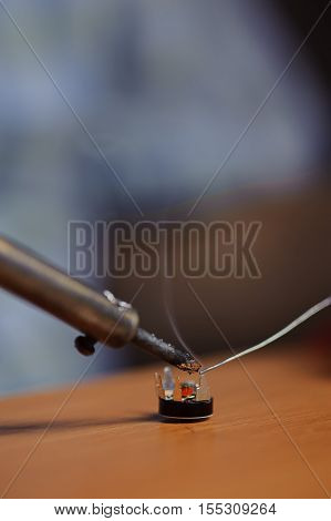 Soldering iron and chip with wire on table closeup