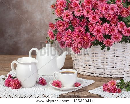 Bouquet of chrysanthemums in a basket and milk tea. Rural concept.