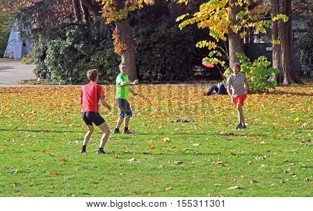People Are Playing Frisbee In City Park
