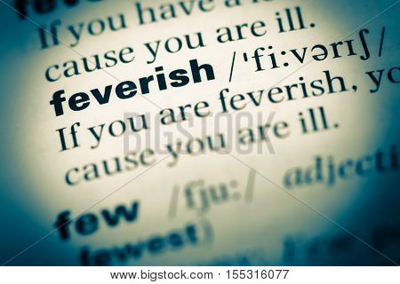 Close Up Of Old English Dictionary Page With Word Feverish