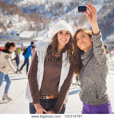 Image of funny teenagers girls taking selfie at ice rink outdoor. Medeo stadium. Ice skating. Almaty. Winter activities for good mood and healthy mind. Healthy lifestyle and sport