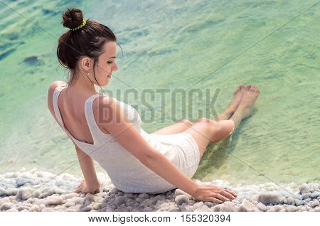 Sexy attractive girl in white dress sits near water of the Backunchak lake with her legs lowered into emerald sea. Young woman relaxing sitting on the edge of salt lake on white crystals of salt. Back to camera