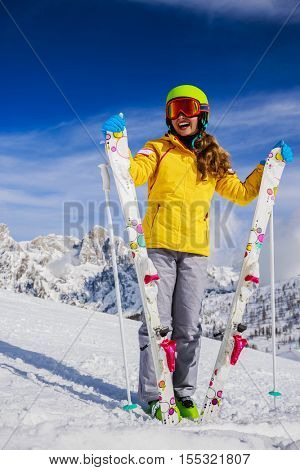 Smiling girl standing with ski and  arms spreading wide open on the fresh powder snow at sunny day in mountains. Italy, San Martino di Castrozza, Alps.