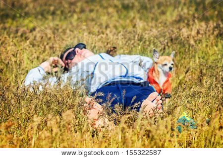 A sexy attractive girl wears the white clothes lies in a field with her small dog. Her hands behind her head. Young woman wears sunglasses relaxing laying on yellow grass of Astrakhan steppe near the Baskunchak salt lake. She is smiling fron to camera