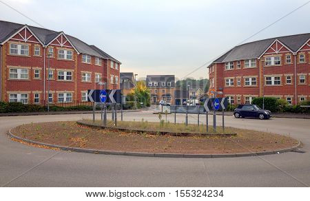 Bracknell,England - October 25, 2016: A car in a traffic roundabout at the entrance to a modern housing estate between two apartment blocks in Bracknell,England