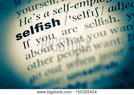 Close Up Of Old English Dictionary Page With Word Selfish