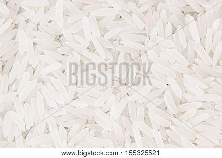 White jasmine rice close-up background. Heap polished long rice for vegetarians.