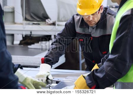 Group of industrial factory workers working with CNC machine