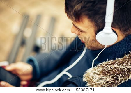 Close up of young handsome man enjoying music with headphones. Selective focus on eye