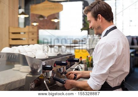 Young waiter making coffee at coffee shop. Happy barman poring coffee from coffee machine. Smiling man with apron preparing coffee for customer in his small business.