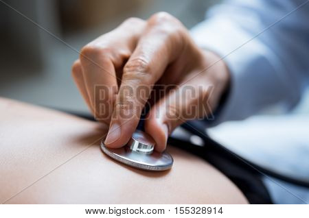 Doctor examining patient with stethoscope. Close up of a doctor hand listening to stethoscope beat while testing patient. Patient visiting doctor for regular check up.