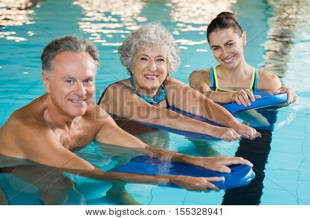 Happy senior couple taking swimming lessons from young trainer. Smiling old woman and mature man doing aqua aerobics exercise in swimming pool. Retired people in swimming pool looking at camera.