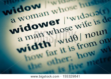 Close Up Of Old English Dictionary Page With Word Widower