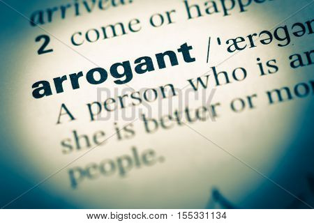 Close Up Of Old English Dictionary Page With Word Arrogant