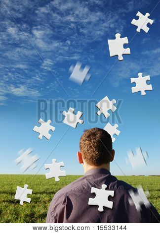 A businessman with white puzzle pieces.