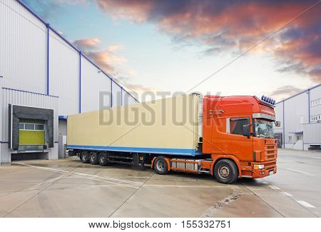 Truck in unloading in warehouse at sunset