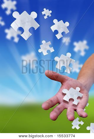 Conceptual photography with a puzzle piece falling on a man's open palm.