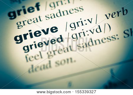 Close Up Of Old English Dictionary Page With Word Grieve