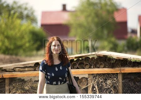 A beautiful redhead is walking towards the camera. Village and idyllic small-town atmosphere with young woman bathed in sunshine. Natural Insect houses in the background. Young smiling flecked mother.