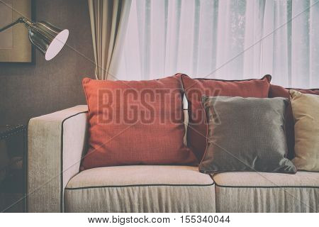 Red And Deep Brown Linen Pillows On Beige Linen Sofa With A Brass Lamp In Modern Classic Living Room