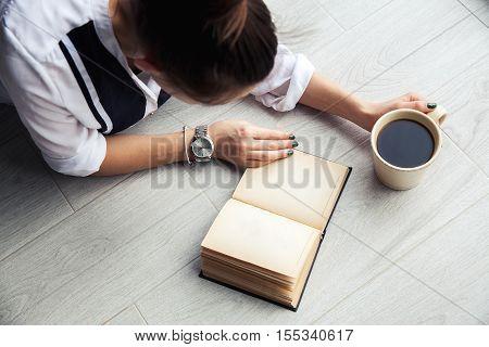 Stylish Girl Reading A Book Lying On The Floor. Beautiful Green Manicure. Clock. A Bracelet. Educati