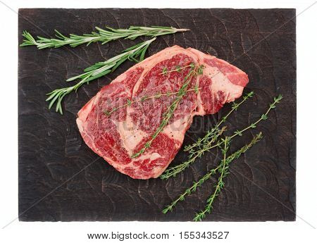 Raw rib-eye steak with herbs on cutting board, isolated