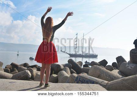 Woman waving goodbye welcome at a tall ship regatta at a seaport.