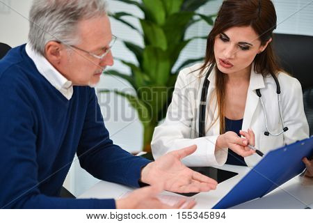 Doctor talking to his patient and showing documents. Focus on the doctor