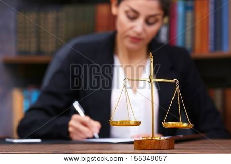 Scales of justice on wooden table and female lawyer on background