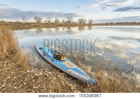 FORT COLLINS  CO, USA - November 5, 2016: All Star racing stand up paddleboard by Starboard in brushed carbon layout with Werner paddle and duffel on a shore of a calm lake with late fall scenery