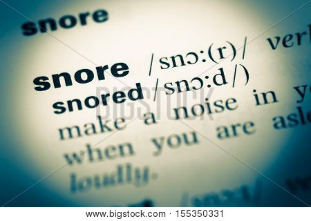 Close Up Of Old English Dictionary Page With Word Snore