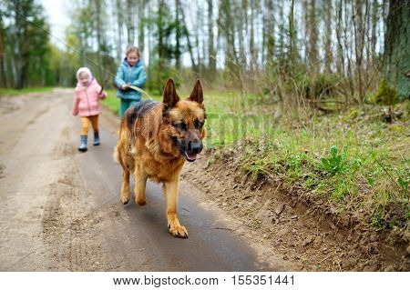 Two Funny Little Sisters Walking Their Dog On A Forest Hike
