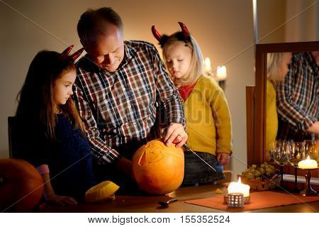 Two pretty young sisters in halloween costumes and their grandpa carving a pumpkin together on Halloween