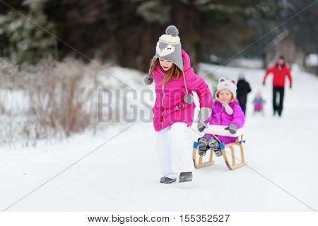 KIds enjoying sleight ride on snowy winter day