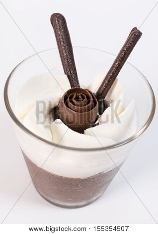 A cup of chocolate mousse with chocolate rose and whipped cream on top