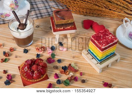A piece of chocolate pie rainbow cake strawberry tartlets and a cup of chocolate mousse on wooden backdrop with selective focus