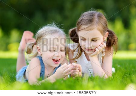 Two Cute Little Sisters Having Fun Together On The Grass